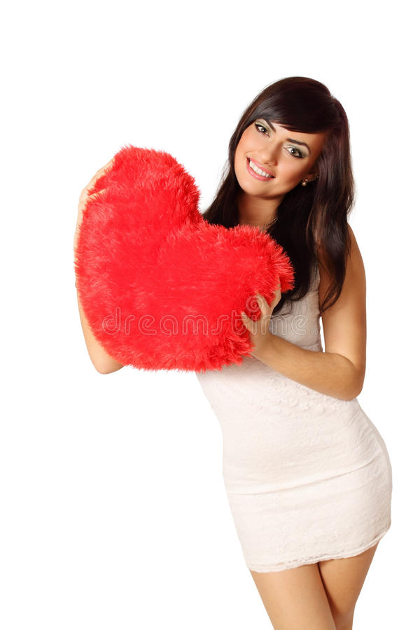 Woman holding heart-shaped pillow stock image
