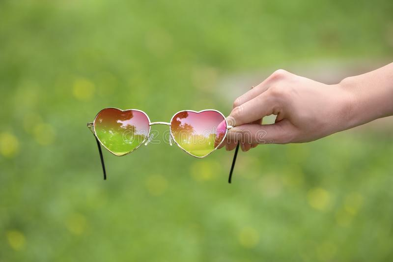 Woman holding heart shaped sunglasses on blurred background royalty free stock photos