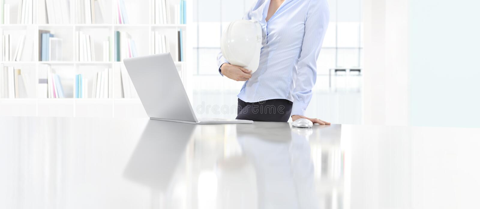 Woman holding an helmet work at desk with computer in office, pr royalty free stock photography