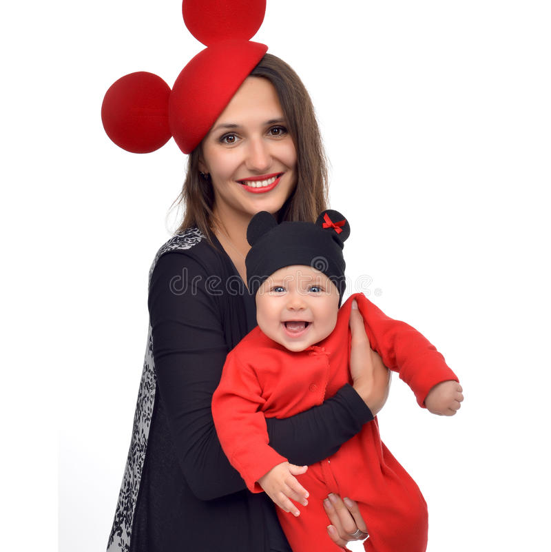 Woman holding in her arms new born infant child baby kid girl. Young mother women holding in her arms new born infant child baby kid girl in red funny hat royalty free stock photography