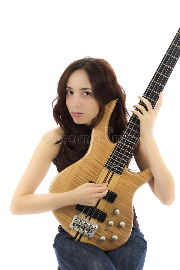 Woman holding her bass guitar up and playing royalty free stock image