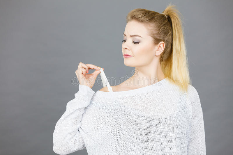 Woman holding her bra strap. From under her sweater. Brafitting concept. Grey background stock images