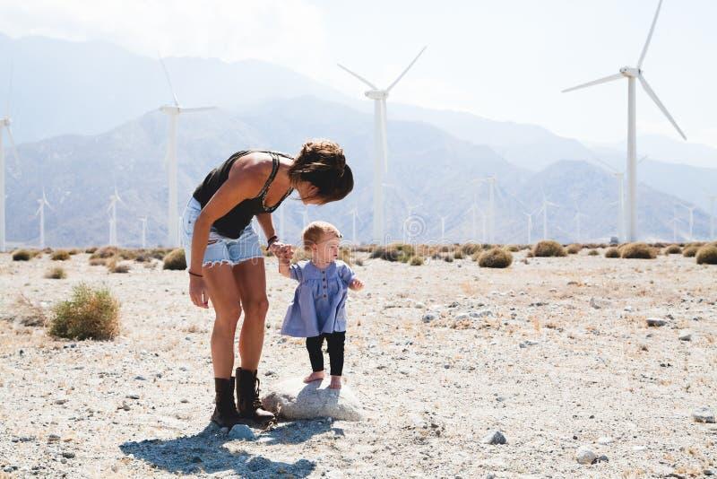 Woman Holding Her Child Walking Near Windmills royalty free stock image