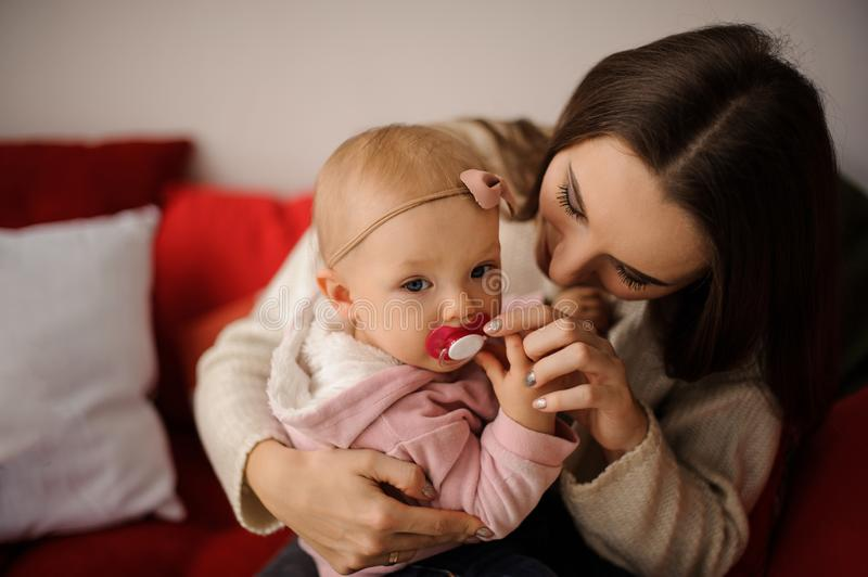 Woman holding her cute little daughter on hands and help her with a baby`s dummy royalty free stock photos