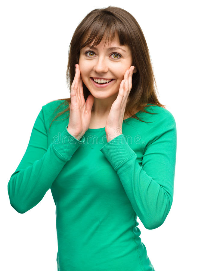 Woman is holding her face in astonishment. Young woman is holding her face in astonishment, isolated over white royalty free stock images