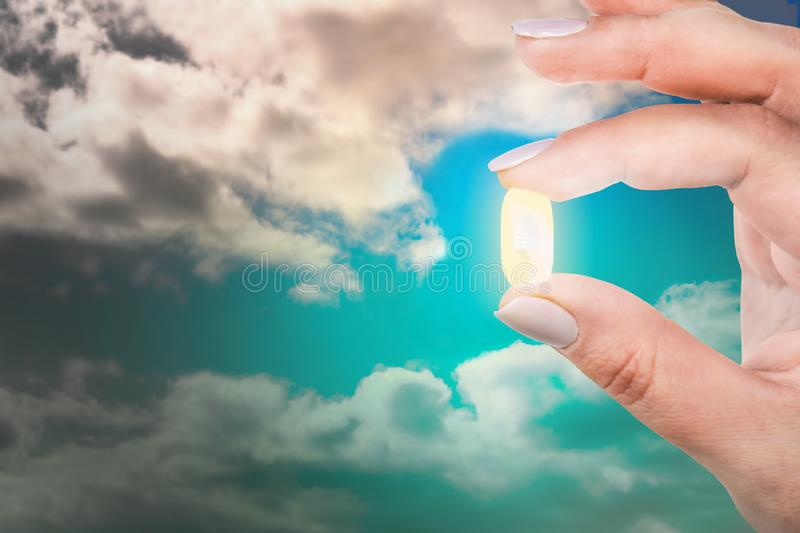 Woman is holding her fingers an antidepressant capsule against the blue sky. Exit from depression royalty free stock image