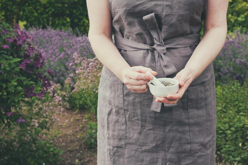 Woman holding in her hands a mortar of healing herbs. Herbalist collects medicinal plants in garden. Woman holding in her hands a mortar of healing herbs stock image