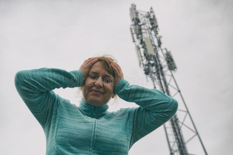 Woman is holding her head near the 5G BTS stock photography