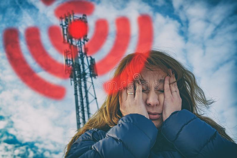 Woman is holding her head near the 5G BTS stock image