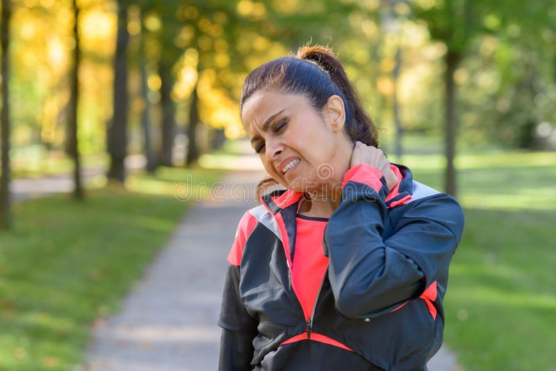 Woman holding her painful neck in park. Adult woman holding her painful neck after exercising in park stock images