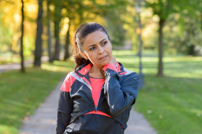 Woman holding her painful neck in park. Adult woman holding her painful neck after exercising in park and looking to the side royalty free stock photo