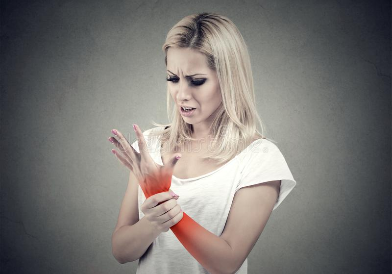 Woman holding her painful wrist. Sprain pain location indicated by red spot. Woman holding her painful wrist isolated on gray wall background. Sprain pain stock photography