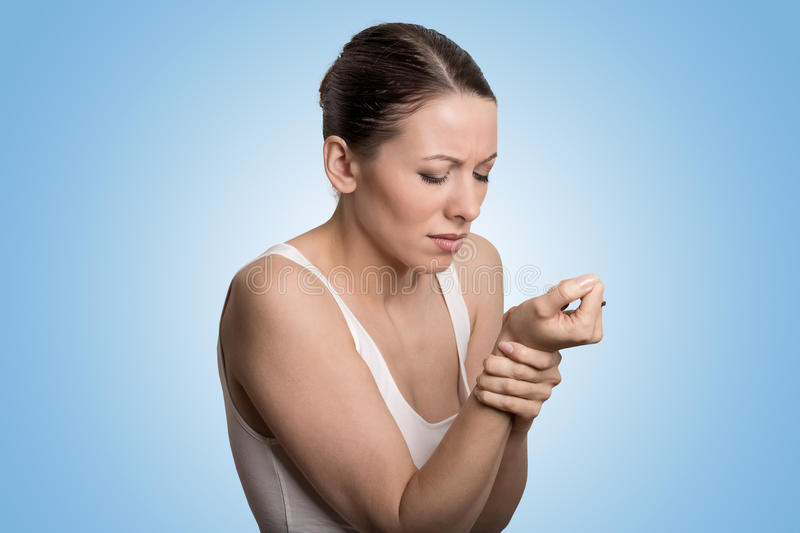 Woman holding her painful wrist. Young woman holding her painful wrist isolated on blue background. Sprain pain location stock photography