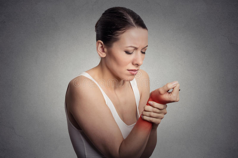 Woman holding her painful wrist. Young woman holding her painful wrist isolated on gray wall background. Sprain pain location indicated by red spot stock images
