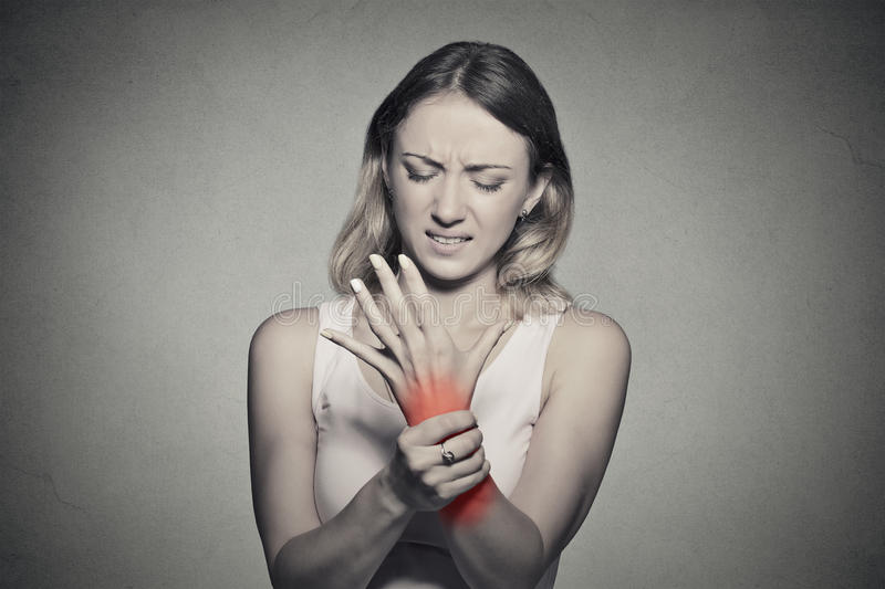 Woman holding her painful wrist. Young woman holding her painful wrist isolated on gray wall background. Sprain pain location indicated by red spot. Negative royalty free stock image