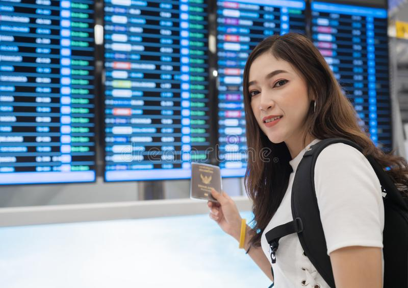 Woman holding her passport with flight information board in international airport royalty free stock images