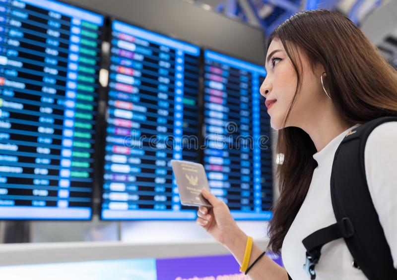 Woman holding her passport with flight information board in international airport stock photo
