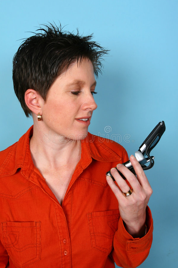 Woman holding her phone. Young woman looking and holding her cellphone stock photo