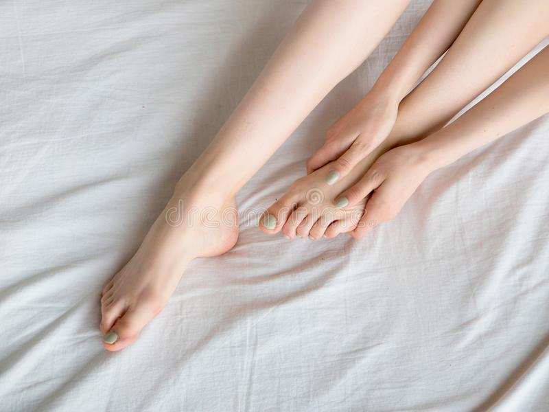 Woman Holding her Tired Feet in Hand Sitting on Bed with White Sheets. stock photography