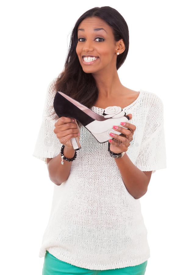 Woman holding a high heel shoe in her hands. Happy african american woman holding a high heel shoe in her hands royalty free stock photos