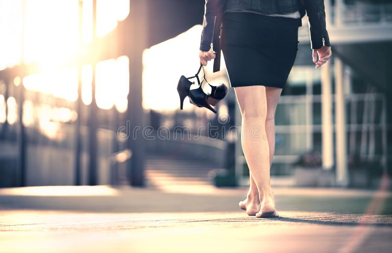 Woman holding high heels in hand and walking home from party barefoot. Businesswoman took off uncomfortable shoes. royalty free stock photography