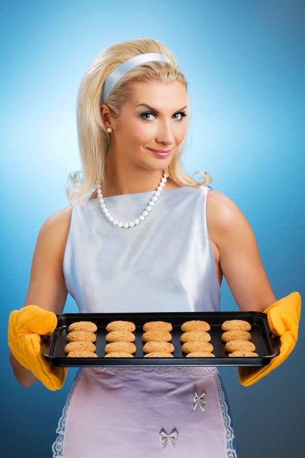 Woman holding hot roasting pan. Beautiful woman holding hot roasting pan with oat cookies on it. Retro stylized portrait stock image