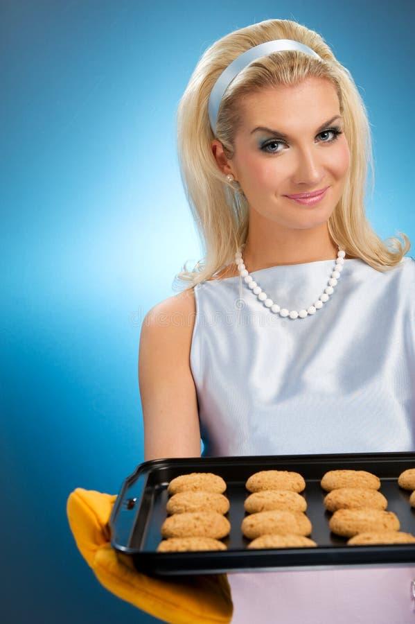 Woman holding hot roasting pan. Beautiful woman holding hot roasting pan with oat cookies on it. Retro stylized portrait stock images
