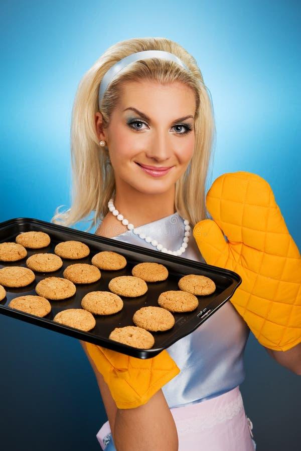 Woman holding hot roasting pan. Beautiful woman holding hot roasting pan with oat cookies on it. Retro stylized portrait stock photos