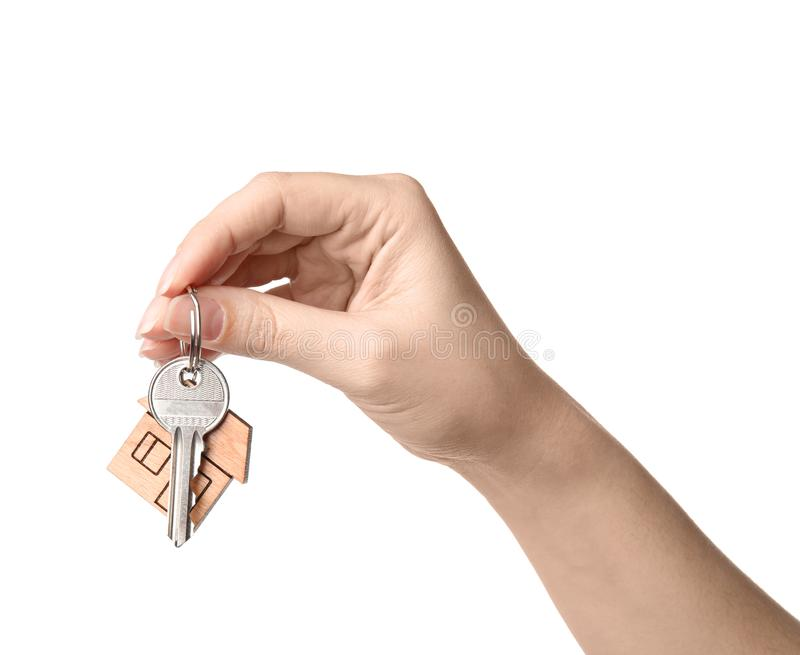 Woman holding house key with trinket on white background. Closeup royalty free stock photography