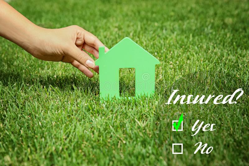 Woman holding house model on green lawn. Real estate agent concept stock photography
