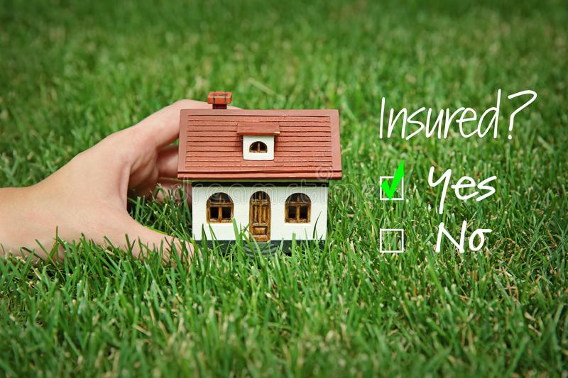 Woman holding house model on green lawn. Real estate agent concept royalty free stock photo
