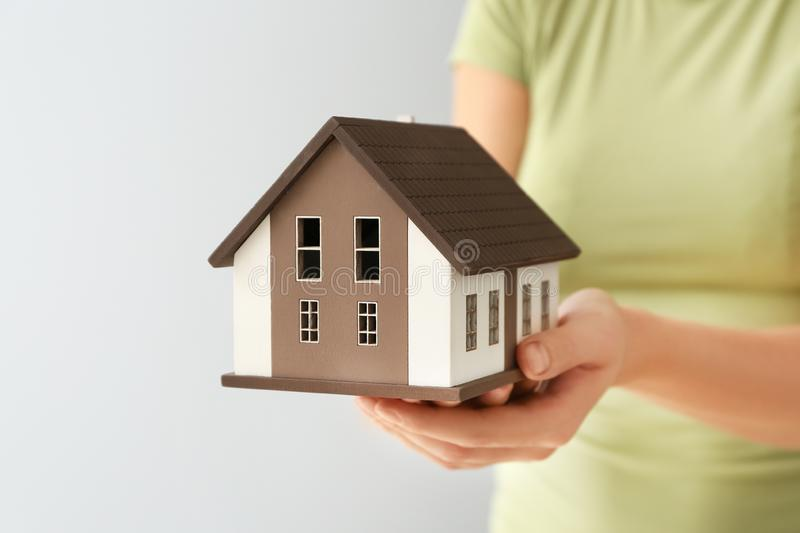Woman holding house model on grey background, closeup. Mortgage concept stock photos