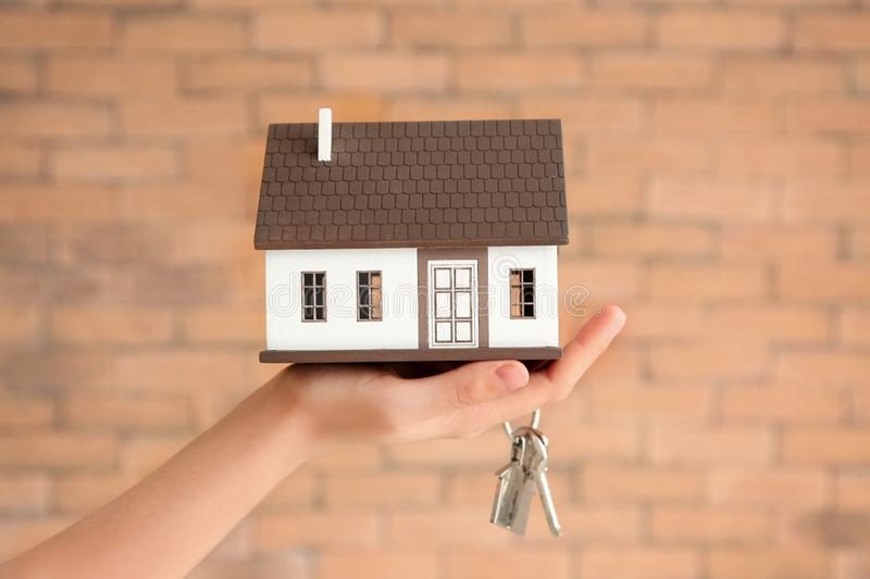 Woman holding house model and key against brick wall. Mortgage concept royalty free stock photos