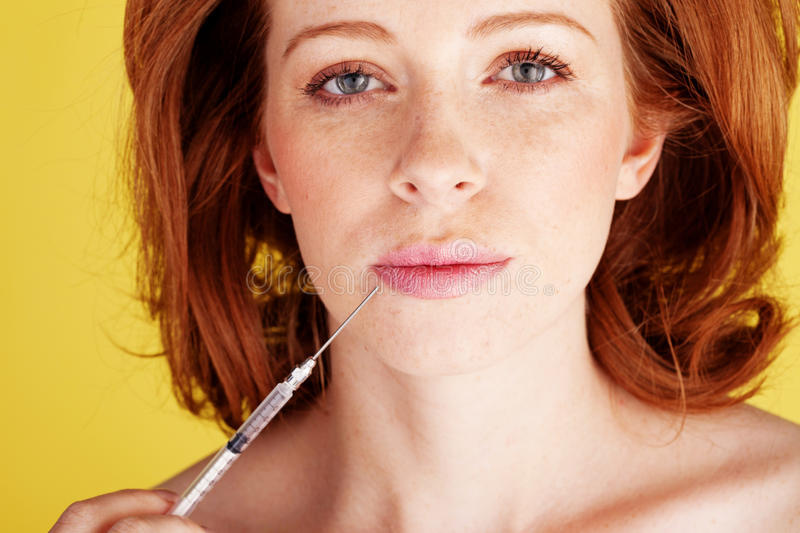 Woman Holding Hyperdermic Needle. Filled with a liquid in front of her face royalty free stock image
