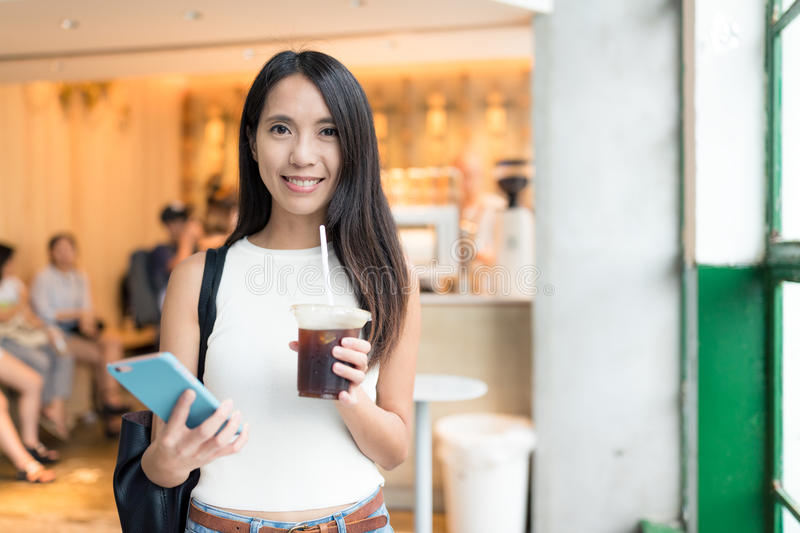 Woman holding iced coffee and cellphone royalty free stock image