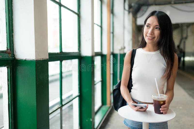 Woman holding iced coffee and looking out of window stock photo