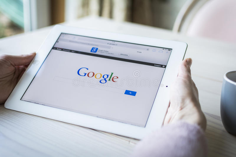 Woman holding iPad showing google search page stock photo