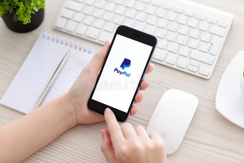 Woman holding iPhone 6 with PayPal on the screen. Alushta, Russia - October 25, 2014: Woman holding a iPhone 6 Space Gray with service PayPal on the screen royalty free stock photography