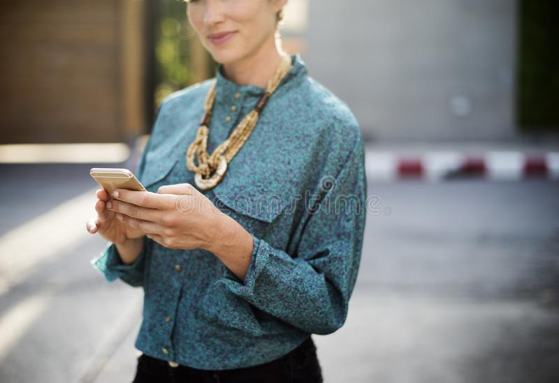 Woman Holding Iphone Wearing Long-sleeved Shirt And Gold Necklace stock photography