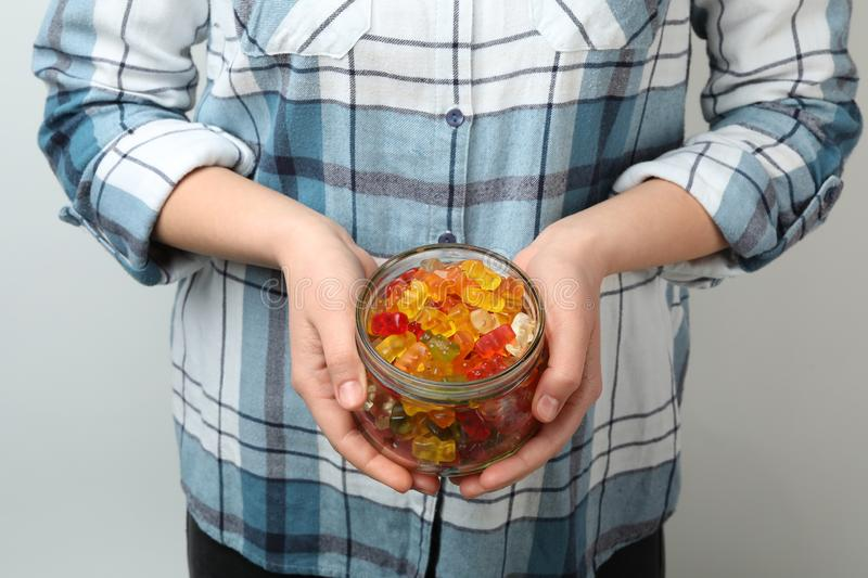 Woman holding jar of colorful jelly bears on light background stock image
