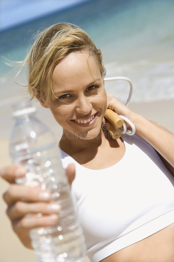 Woman holding jump rope and water bottle. stock photo