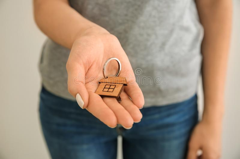 Woman holding key with trinket in shape of house, closeup royalty free stock photo