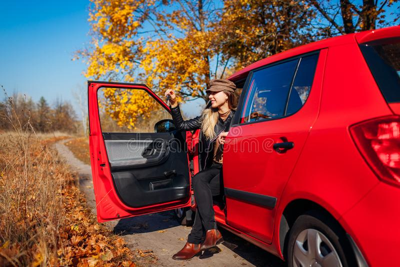 Woman holding keys of new car. Happy buyer purchased red autimobile. Driver sitting in auto stock photo