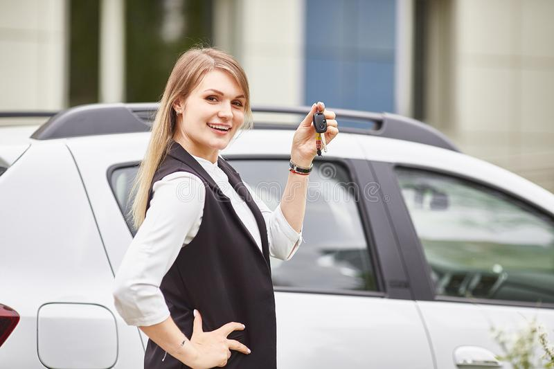 Woman holding keys to new car auto and smiling at camera stock photography