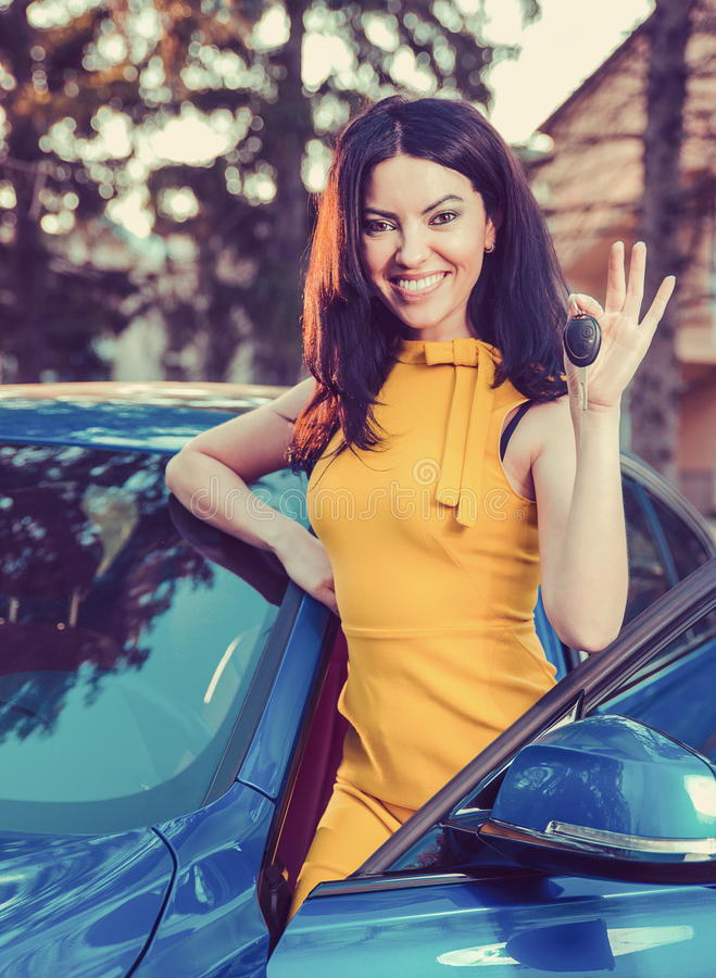 Woman holding keys to new car and smiling at camera on a background of a house. Young woman holding keys to new car and smiling at camera on a background of a stock image
