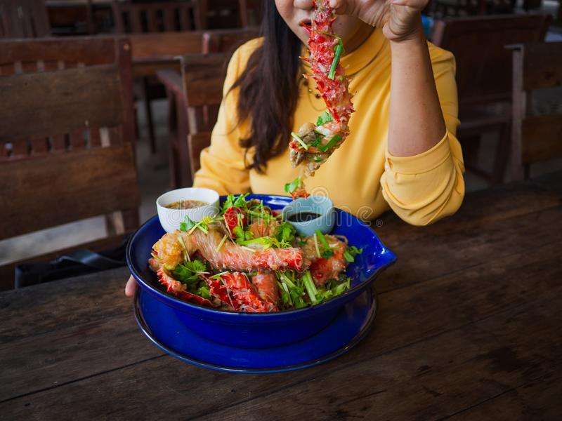 Woman holding king crabs Alaska leg with wooden table and chairs.  stock photo