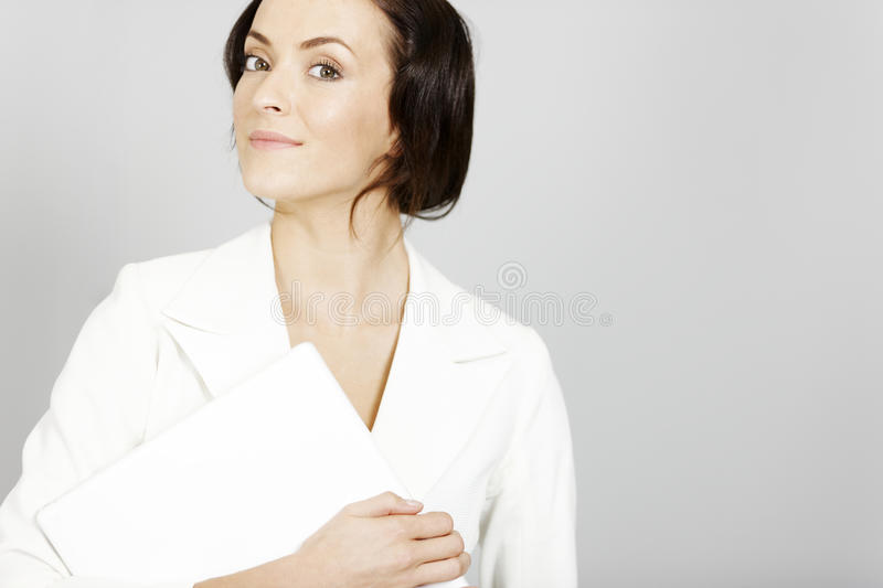 Woman holding laptop. Business woman in white suit holding a laptop stock photo