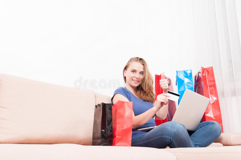 Woman holding laptop and card showing like. Woman sitting on couch holding laptop and card showing like gesture with shopping bags around with copy text space stock photo