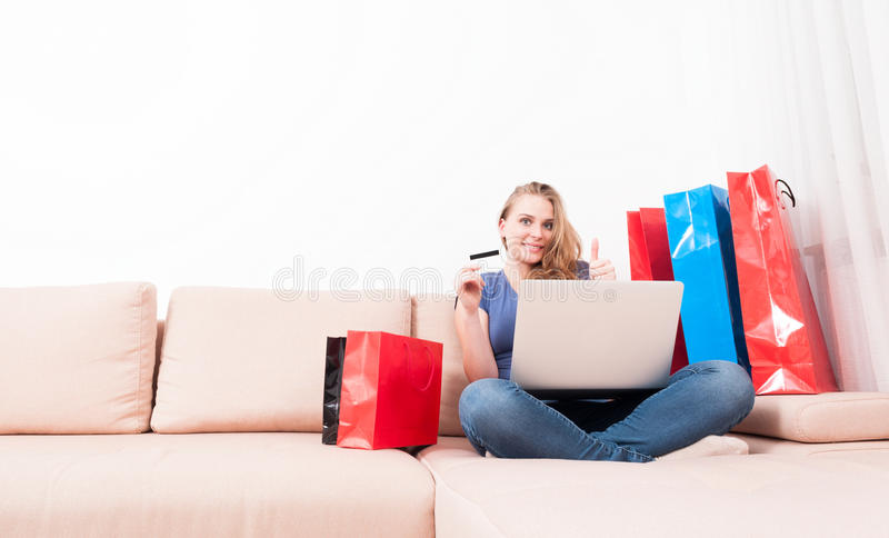 Woman holding laptop and card showing like. Woman sitting on couch holding laptop and card showing like gesture with shopping bags around with copy text space royalty free stock photography
