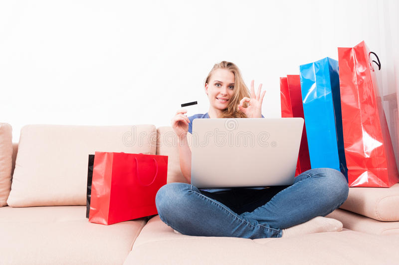 Woman holding laptop and card showing okay. Woman sitting on couch holding laptop and card showing okay gesture with shopping bags around with copy text space stock photos